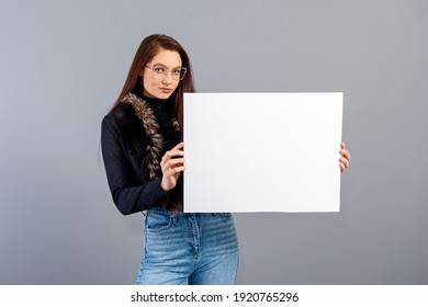 elegant young teenager woman showing blank signboard with copy space, isolated on gray