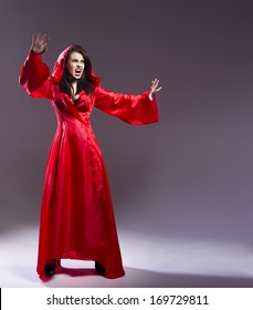 Elegant young witch in a red clothes cast magic spell