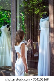 Elegant young woman admiring beautiful white wedding dress, touching show window of bridal boutique. Dreaming about wedding concept.