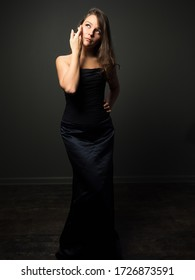Elegant young woman in black cocktail dress