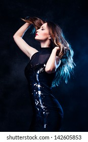 elegant young woman in black dress profile studio shot blue back light