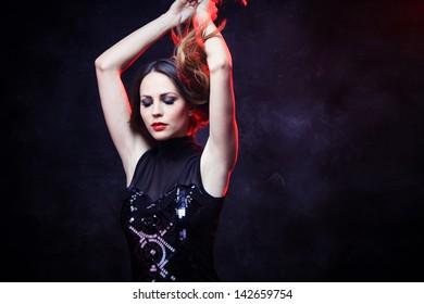 elegant young woman in black dress  studio shot red back light