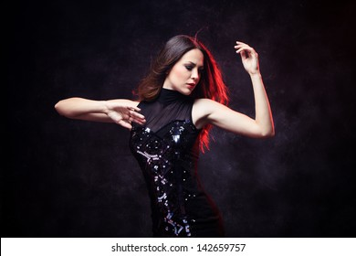 elegant young woman in black dress  dancing red back light studio shot