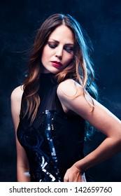 elegant young woman in black dress  studio shot blue back light