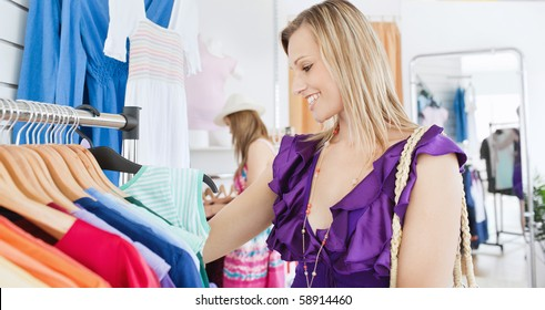 Elegant young woman choosing clothes with her friend in a shop