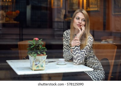 Elegant young woman in a classy cafe. Urban shot