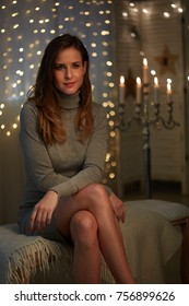 Elegant young woman in a dark room with christmas lights.