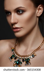 Elegant young woman with evening smart make up and sparkling necklace jewelry on her neck. Gorgeous woman face.