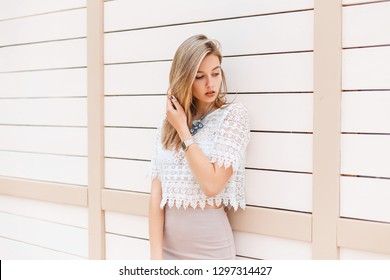 Elegant young woman in a fashionable beige skirt in a white lace blouse with an ornament is standing near a vintage white wooden wall outdoors on a sunny spring day. Glamor girl enjoys the weekend.