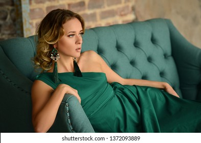 Elegant young woman in green evening dress posing in vintage interior