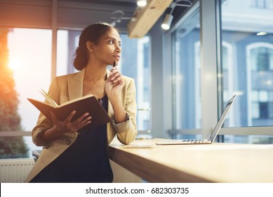 Elegant young woman looking away thoughtfully while holding notepad and leaning on table with laptop. Successful Afro American female pondering about business strategy for enterprise