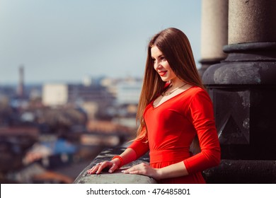 Elegant young woman looks confident while leaning over the stone balcony