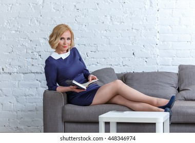Elegant young woman lying on a comfortable sofa with her diary