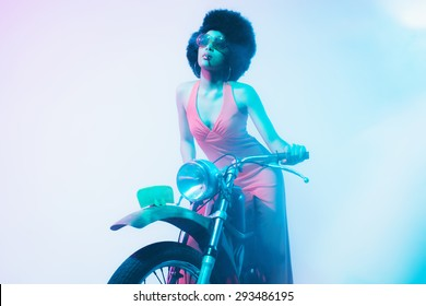Elegant Young Woman Posing on her Vintage Motorcycle While Smoking a Cigarette Against White Background.