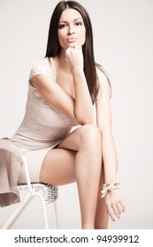 elegant young woman in short dress,  sit on chair, studio shot