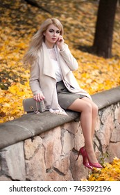 elegant young woman walking in autumn park