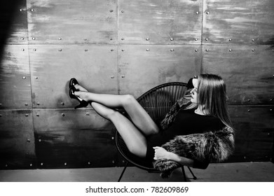 Elegante blonde girl wear on fur coat and combi dress posed on chair against steel wall on studio.