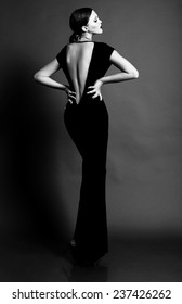 Elegante monochrome fashion photo of glamour beautiful brown-haired woman in a black sexy dress with open back wearing gold jewelry and posing in the studio,luxury