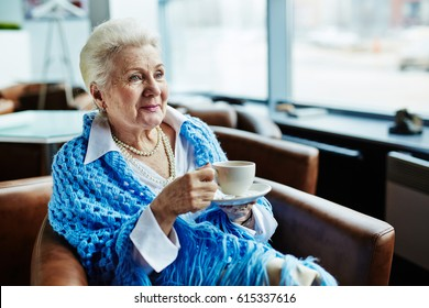 Elegant-looking elderly woman with cornflower blue knitted shawl on shoulders holding cup of delicious coffee in hands, sitting in comfortable armchair and enjoying picturesque view from window