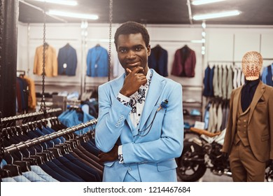 Elegantly dressed African man posing with hand on chin while standing in a classic menswear store.