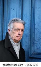 Elegantly dressed, distinguished older man, silver grey hair, portrait, with blue distressed door background. Chelsea, London, December 2017.