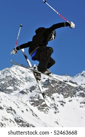 an elegantly dressed freestyle  ski jumper in black and white clothes against a back drop of mountains.