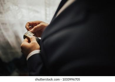 an elegantly dressed man sets his watch