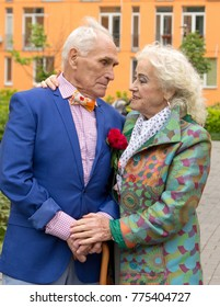 Elegantly dressed old man and old woman walking outdoors  near the multi-colored apartment blocks