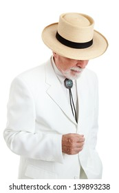 Elegantly dressed senior man from the American South or the Islands, wearing a white suit, string tie, and straw Panama hat.  Isolated on white.