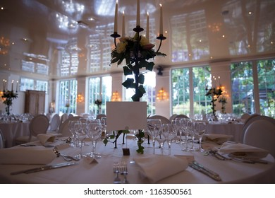 elegantly served with glasses, cutlery and decorated with flowers tables with white tablecloths and burning candles in candlesticks in the blurred background of the fashionable restaurant hall.