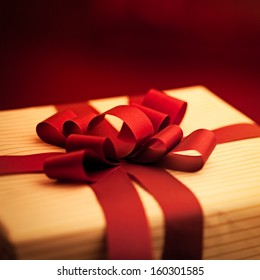 Elegantly wrapped present with a red ribbon.