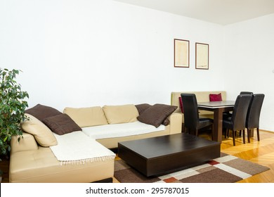 Elegent large living room with  stylish dining table and chairs next to. Apartment for business meetings and rest from work. Modern design of home with sofa corner. Pleasant interior, indoor photo.