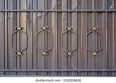 Element of architectural decorative exterior metal fence. Metal gates with forged pattern of symmetrical parts with twisted vertical posts. Forged iron ornament of gate lattice as background