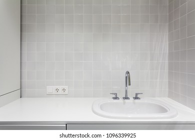 Element of bathroom interior. New wash basin, white sink and tile.