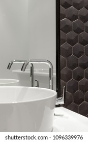 Element of bathroom interior with white sink and large mirror. New wash basin and black hexagonal tiles tile.