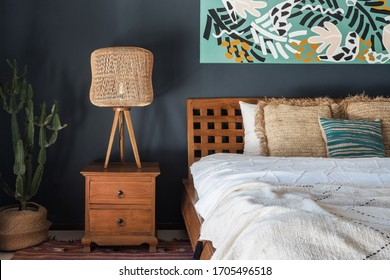 Element of bedroom interior at modern house with ethnic decor, lamp on wooden nightstand table, paint on wall, comfortable bed and green cactus plant in basket