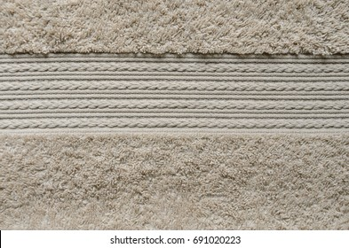Element of beige color towel. Fleecy part and decorative element with braided pigtails. Texture is similar to the texture of a fleecy knotted-pile carpet.