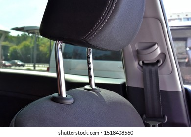 Element of car headrest with metal protect element, selective focus and blurred sea belt on background. Automobile interior with part of headrest. chrome protection element. passenger safety in a car