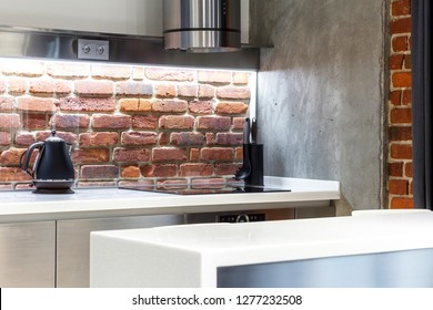 Element of loft kitchen with red brick wall, light and different equipment in luxury interior concept