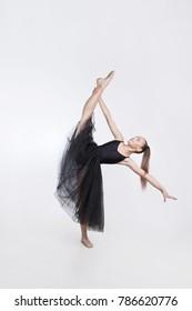 Element of rhythmic gymnastics. Graceful dancer girl balances on one leg. Sportswoman performs the exercise battement isolated on white background