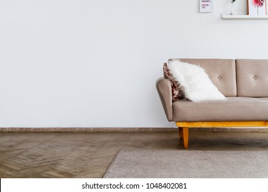 Element of a stylish beige sofa with a white fluffy pillow against a white wall background
