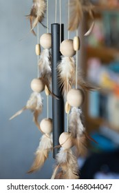 Element of a traditional Native American souvenir made of feathers, rope and wooden balls with a bell