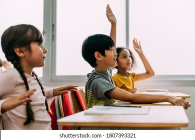 Elementary age Asian student boy raised hands up in Q and A class. Diverse group of pre-school pupils in elementary age in education building school. Volunteering and participating classroom concept.