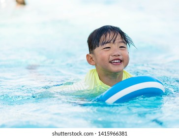 Elementary Age Boy Smiling and Swimming in Pool at Recreation Center