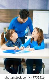 Elementary age children listening to female teacher in school classroom. Smiling, happy.