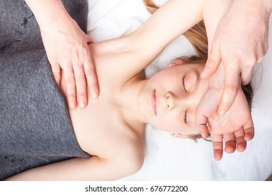 Elementary age girl's arm being manipulated by osteopathic manual therapist or physician