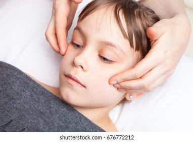 Elementary age girl's cheeks being manipulated by osteopathic manual therapist or physician