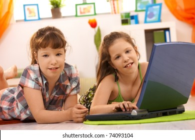 Elementary age girls playing computer game on laptop at home, looking at camera, smiling.