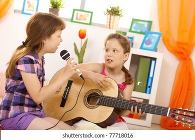 Elementary age girls playing music and singing together at home, having fun.?