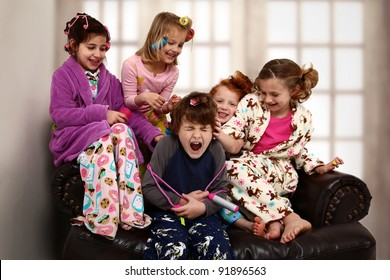 Elementary age girls at slumber party torture brother with hair rollers and makeup.